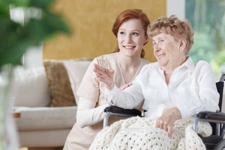 Elder woman is talking with smiling red-haired nurse in common room of senior home