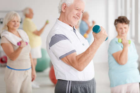 Older man in sportswear training together with his friends using dumbbells Stock Photo