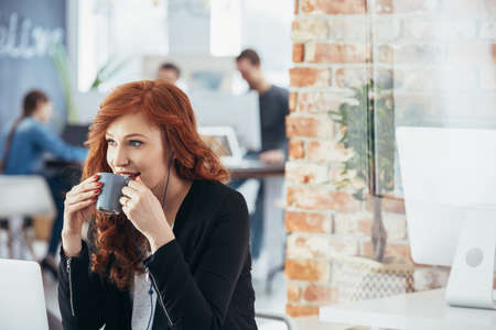 Beautiful young woman drinking coffee in modern office