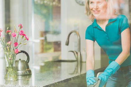 Smiling housewife is cleaning chair in blue gloves in modern kitchen