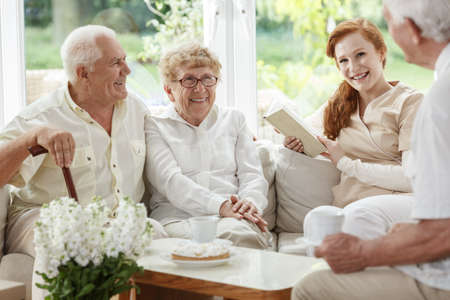 Friendly nurse enjoys meeting with elder people while sitting on beige coach Stock Photo