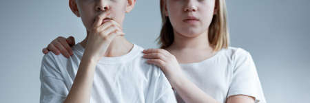 Two children looking scared dressed in white Imagens