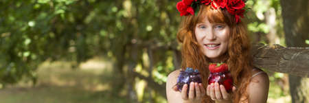 Girl with red flower crown holding fresh fruits Stock Photo