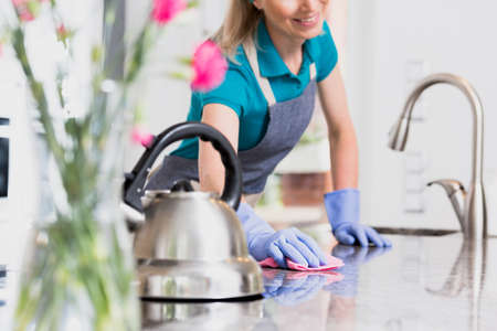 Housewife in an jeans apron and blue rubber gloves leans over clean counter top