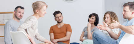 Young man talking about his problem during group psychotherapy