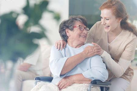 De gelukkige patiënt houdt verzorger voor een hand terwijl samen het doorbrengen van tijd