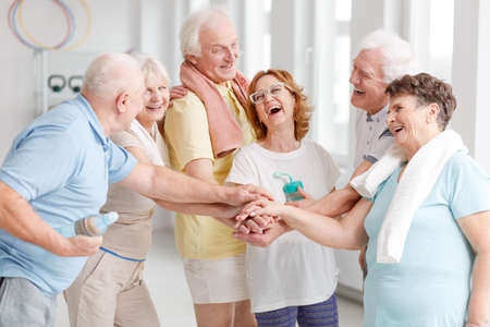 Happy elders gathering hands and laughing before yoga classes
