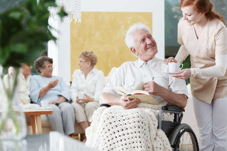 Smiling elder man on wheelchair with braided blanket on legs and reads book
