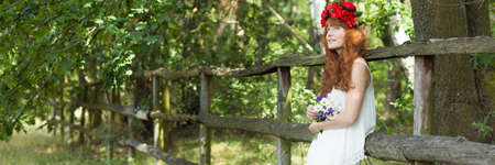 Country girl with red flower crown and bunch of flowers
