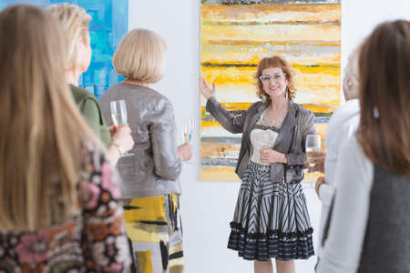 Happy elder artist presenting her painting at the opening Stok Fotoğraf