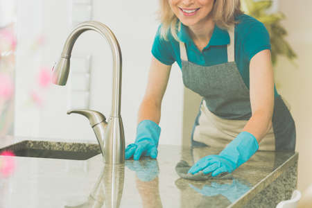 De vrouw veegt tegenbovenkant af en daalt met glanzende afwerking in moderne keuken
