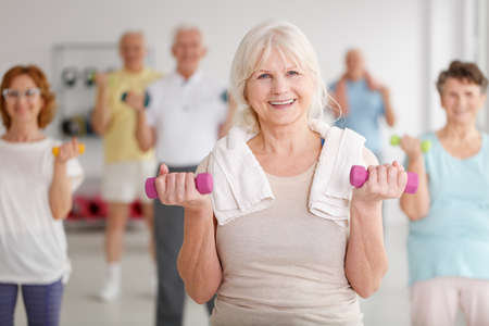 Active happy elders with colorful dumbbells during training