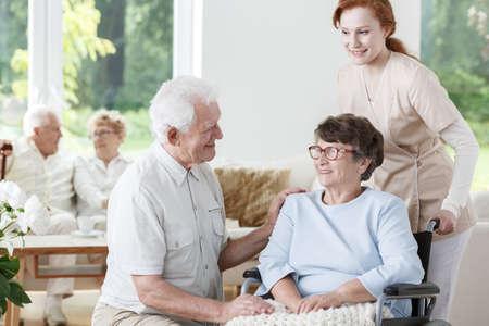 De verpleegster steunt gehandicapte hogere vrouw op rolstoel tijdens vergadering met bezoeker Stockfoto - 83169598