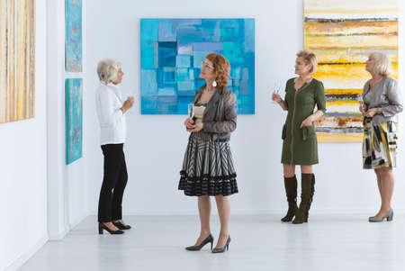 Elegant elder women looking at paintings during opening