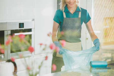 Ragazza bionda che ottiene sacchetti di immondizia durante la pulizia di cereali in cucina