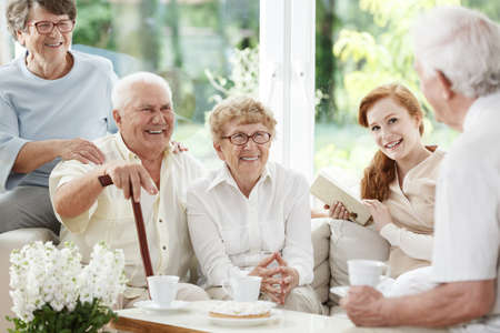Senior people spends time together with young red-haired caregiver Фото со стока