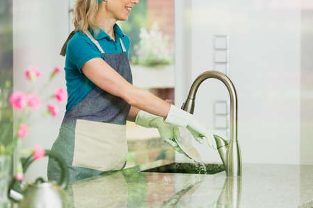 Happy housekeeper washes a plate in kitchen sink with gloves on hands Stock Photo