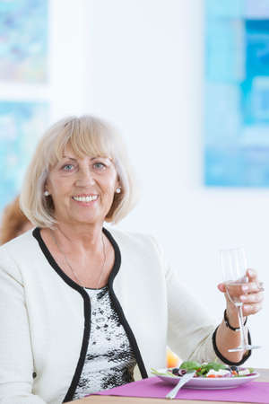 curator: Elder happy lady smiling and holding a glass of champagne