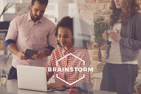 Young workers using laptop and brainstorming in modern office Stock Photo