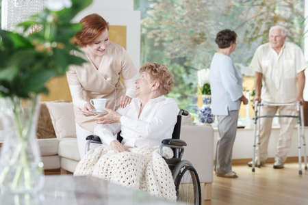 Friendly nurse gives a cup of tea to disabled woman on wheelchair in senior home