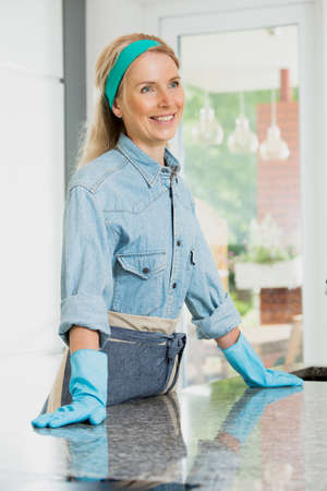 Happy housewife with blue band on head relies on a shiny counter top