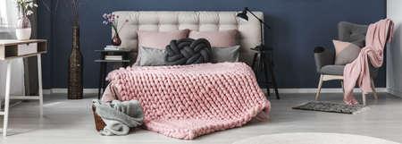 세련된 침실에서 아늑한 침대에 두꺼운 모직 핑크 담요
