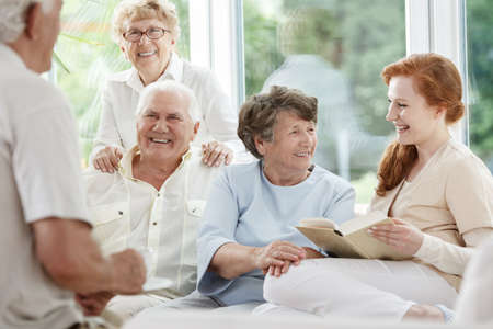 Smiling nurse holds book and sitting next to happy elder people in senior home