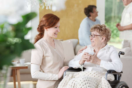 Older woman sits on wheelchair next to nurse and is holding a cup of coffee