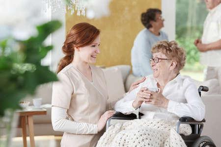 Oudere vrouw zit op rolstoel naast verpleegster en houdt een kopje koffie