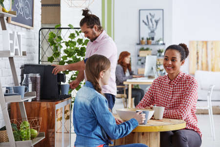 Smiling coworkers drinking coffee in cozy relax zone photo
