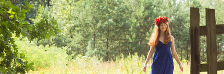 Girl with red flower crown walking along the country Stock Photo