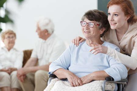 アシスタントは、老人ホームで車椅子の患者に何かを示しています