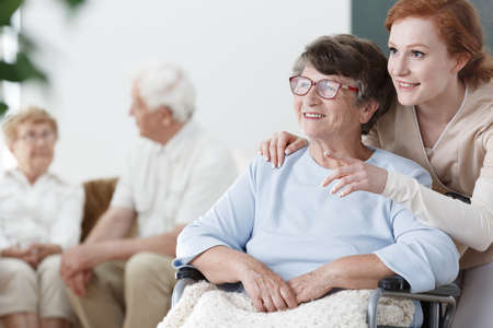 Assistent toont iets aan de patiënt op rolstoel in het senior huis Stockfoto