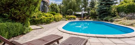 Buiten ovaal zwembad omgeven door tuinplanten