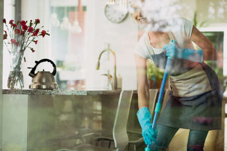 Smiling girl cleans the floor with a mop and blue rubber gloves in large kitchen