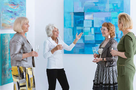 Four happy older women standing and smiling on exhibition