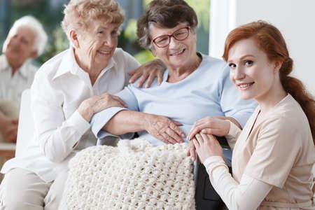 Dos mujeres mayores y amable enfermera están sonriendo durante la reunión en la sala común Foto de archivo - 83291280