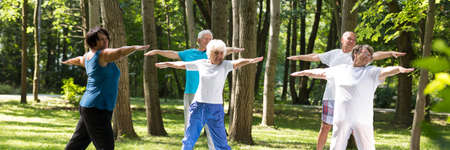 Healthy retirement-training with instructor in city park