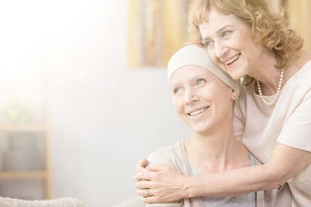 Smiling older woman hugging her friend with cancer wearing a scarf