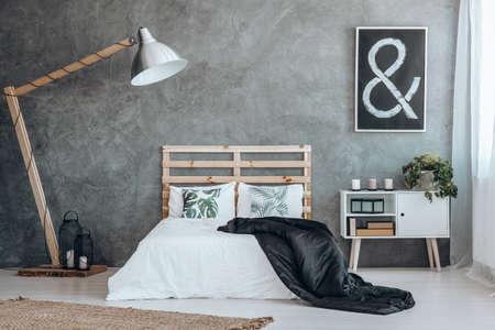 검은 색 방패가 달린 킹 사이즈 침대에 자연스러운 동기가 부여 된 흰색 베개 2 개 스톡 콘텐츠