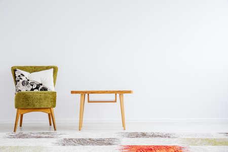 古典的な木製のテーブル、緑の椅子、枕模様のカーペットとシンプルな部屋 写真素材 - 83335097