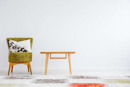 Simple room with classic wooden table, green chair, pillow and patterned carpet