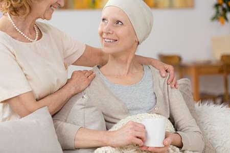 Glimlachende vrouw die kanker lijdt aan tijd doorbrengen met haar vriendin Stockfoto - 83598918