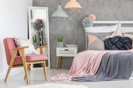 Pink armchair with decorative cushion and big mirror in the bedroom corner