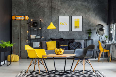 Modern furniture in unique yellow and gray industrial office interior Фото со стока