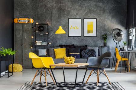 Modern meubilair in uniek geel en grijs industrieel bureaubinnenland Stockfoto