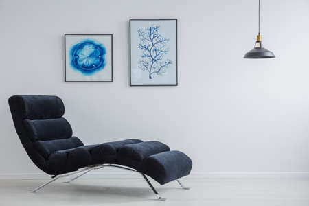 Spacious living room with simple decoration and dark comfortable chaise lounge Stock Photo