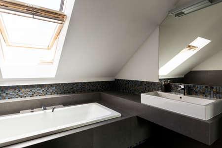 창문이있는 다락방의 밝고 넓은 욕실 스톡 콘텐츠