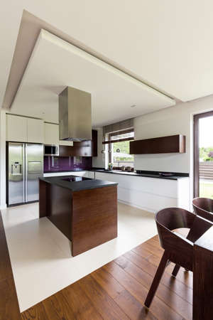 Modern and spacious kitchen with white walls and steely fridge