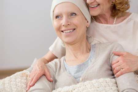 Sick woman with scarf supported by her helpful friend Stock Photo - 83598923